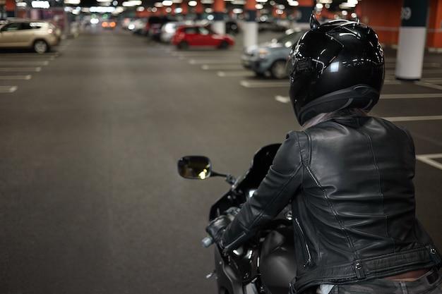 생활, 오토바이, 야간 도시 및 사람들 개념의 활동적인 방식. 주차장에서 오토바이를 타는 안전 헬멧과 검은 색 가죽 재킷을 입은 유행 자신감 여성 바이커의 후면 샷