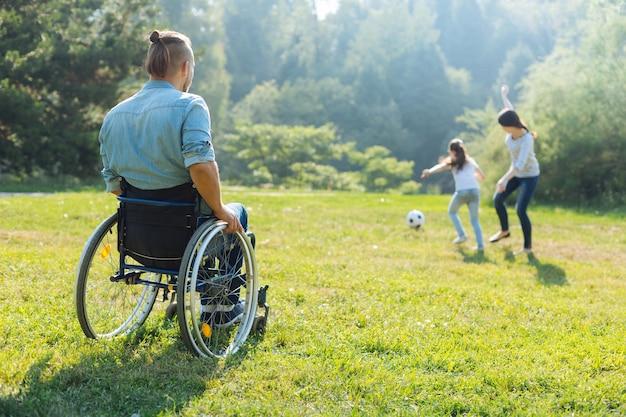 アクティブな週末。牧草地に座って、サッカーをしている彼の最愛の妻と娘を見ている車椅子の若い男の背面図