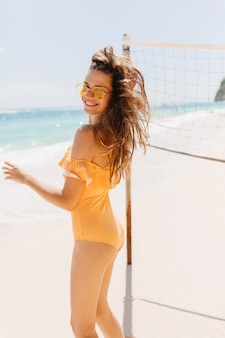 Active white female model in orange swimsuit looking over shoulder while dancing at beach. attractive european girl wears yellow sunglasses playing volleyball at resort.