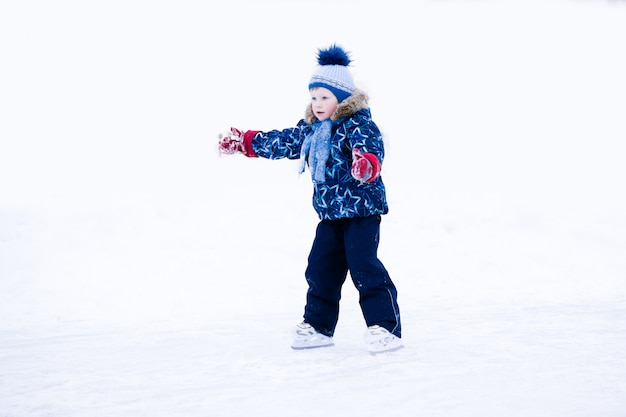 Active winter holiday - cute little boy skating on an ice rink