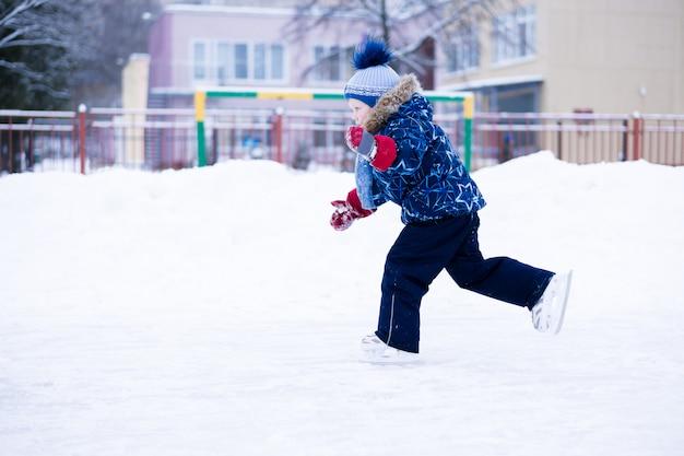Активный зимний отдых - милый маленький мальчик катается на коньках на катке