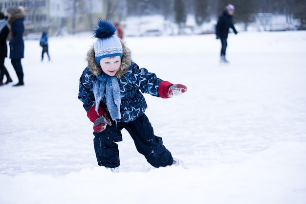 Active winter holiday - cute little boy skating onn ice rink