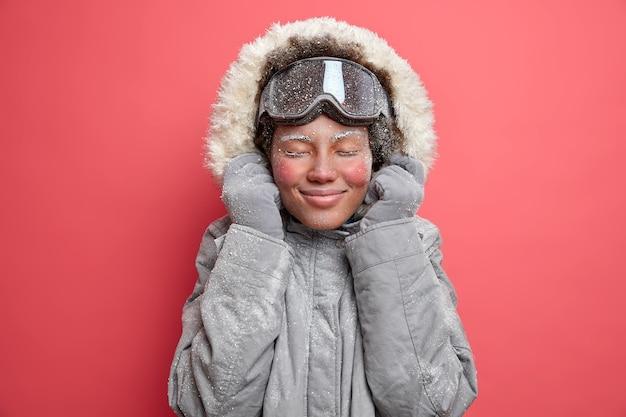 활동적인 겨울 휴식 및 야외 스포츠 개념. 만족 한 여성은 눈을 감고 즐겁게 웃으며 좋아하는 취미로 여가 시간을 즐기고 저온 용 산 드레스를 입고 스노우 보드를 타러갑니다