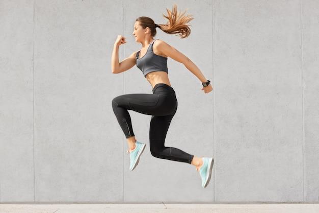 활동적인 여성은 에너지로 가득 차고, 공중에서 높이 뛰며, 운동복을 입고, 스포츠 경쟁을 준비합니다.