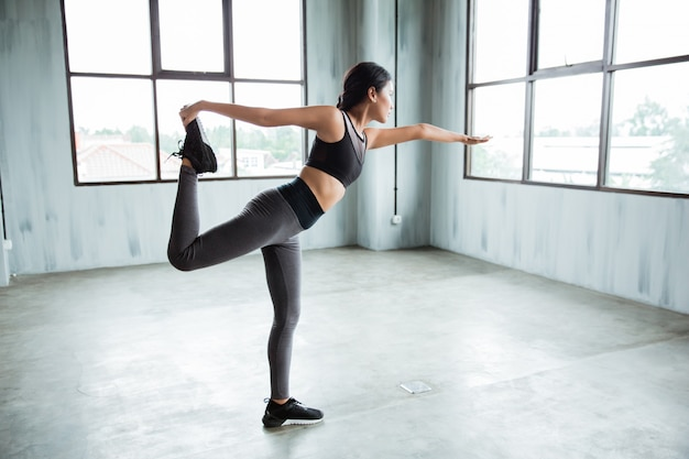 Active woman doing balance movement for stretching her legs