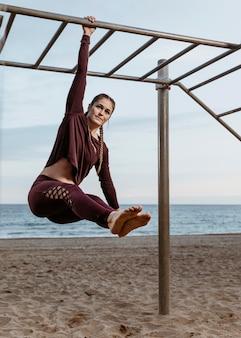 Donna attiva facendo esercizi di fitness all'aperto sulla spiaggia