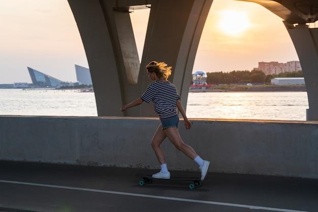 도시와 일몰의 전망을 감상할 수 있는 강을 따라 롱보드에서 여름 저녁 스케이트를 즐기는 활동적인 여성