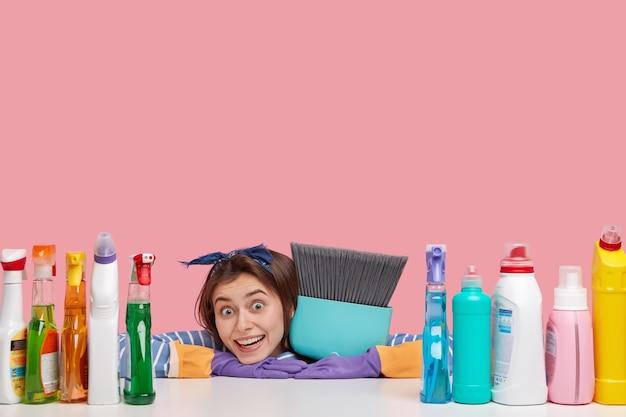 アクティブな女性は家の掃除を楽しんで、新しい洗浄剤を使用し、ほうきを運び、楽しく見え、汚れた表面をほこりを払い、注文に応じてフラットにします