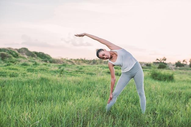 초원에서 운동하는 적극적인 여자