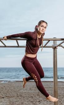 Donna attiva che esercita all'aperto sulla spiaggia