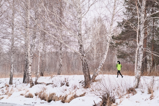 Active woman in green jacket running in winter forest with naked trees
