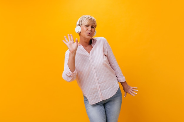 Active woman in headphones sings and listens to music in headphones