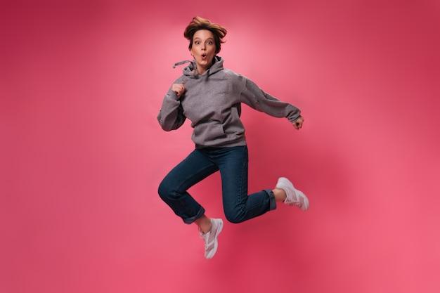 ピンクの背景にジャンプする居心地の良い服装のアクティブな女性。孤立した上を移動するパーカーとジーンズの魅力的な女の子の肖像画