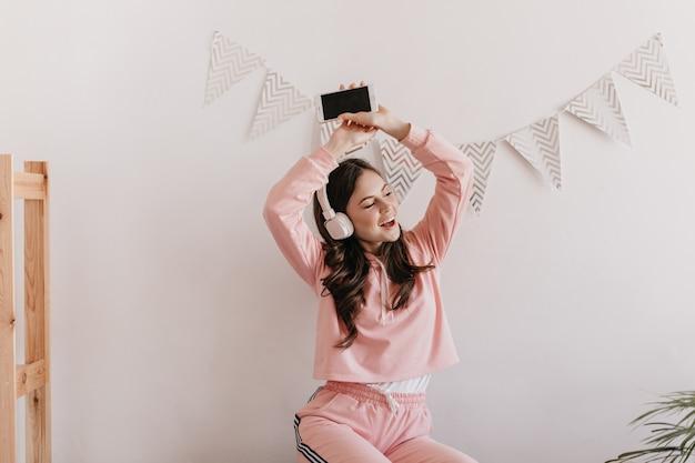 분홍색 정장을 입은 활성 여성이 그녀의 아파트에서 춤을 추고 헤드폰으로 음악을 듣고 있습니다.