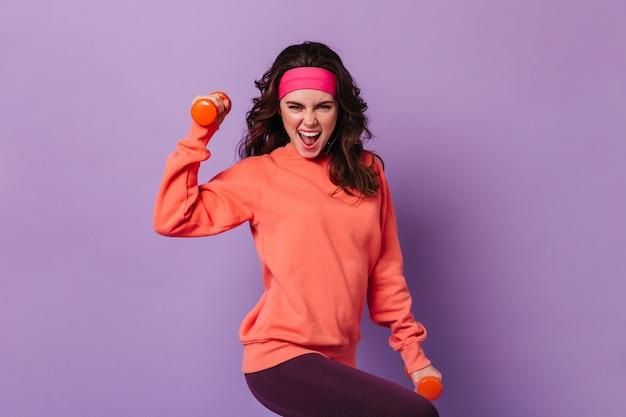 スポーツの明るい服装のアクティブな女性は、ダンベルで手の運動を感情的に示しています