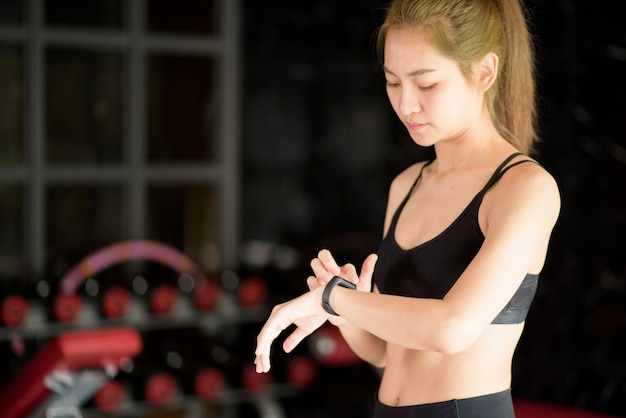 An active woman is using smart watch in fitness gym