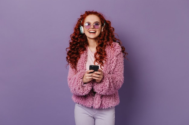 Active woman laughs while listening to music in large headphones. girl in pink woolen jacket and glasses holding phone.