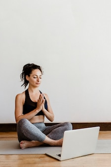 Active woman learning a yoga online via a laptop