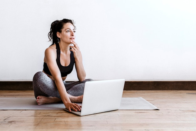 Active woman learning yoga online via a laptop