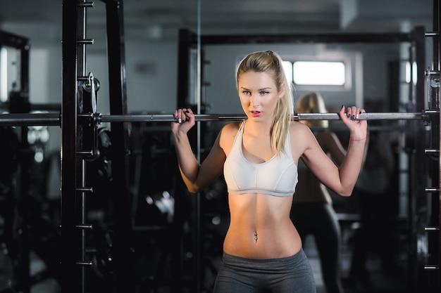 Active woman lifting barbells