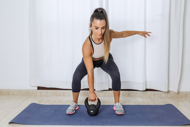 Active woman lifting kettlebell during workout