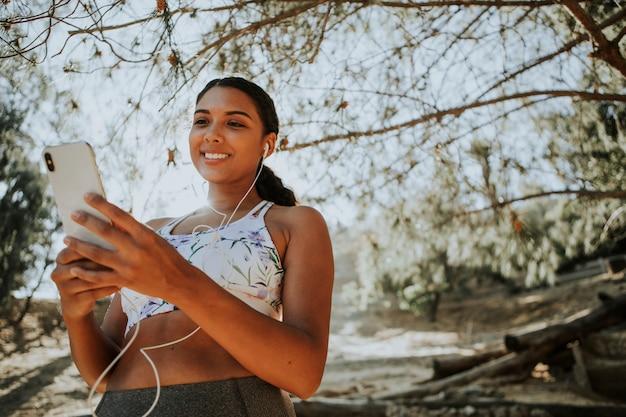 Активная женщина слушает музыку через наушники Premium Фотографии
