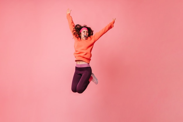 Active woman in orange hoodie and dark leggings vigorously jumping on pink wall
