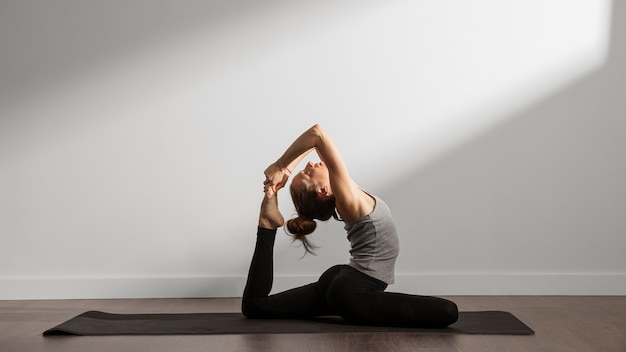 Active woman practicing yoga at home