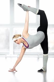 Donna attiva che allunga con una mano sul pavimento