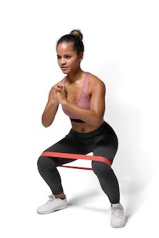 Активная женщина, использующая бедренную повязку в положении на корточках