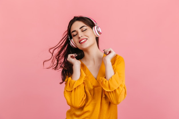 Active woman with snow-white smile is dancing on pink wall. model in orange blouse listening to music.