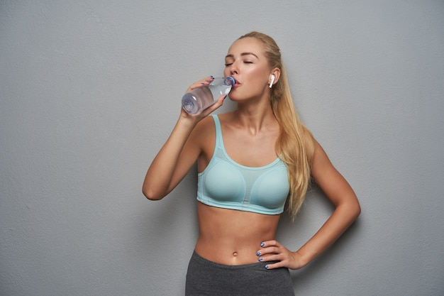 Active young blonde model with ponytail hairstyle wearing mint sporty top and grey leggins while posing over grey background, drinking spring water from bottle with closed eyes