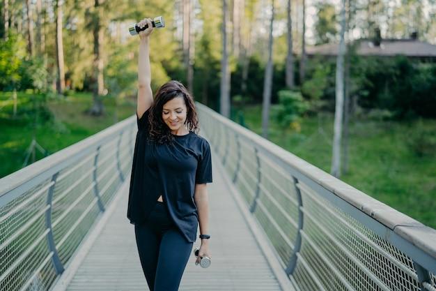 アクティブな若いブルネットのスポーツウーマンは、ダンベルを使ってエクササイズをし、屋外でフィットネスエクササイズを行い、アクティブな服を着て、新鮮な空気を吸い、筋肉に働きかけます。女性、強さとボディービルの概念