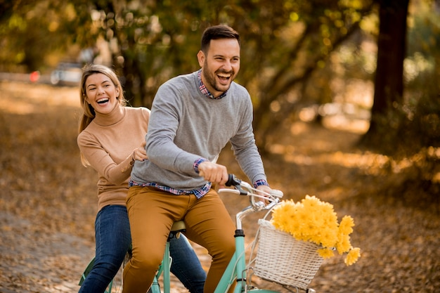 Active young couple enjoying together in riding bicycle in golden autumn park