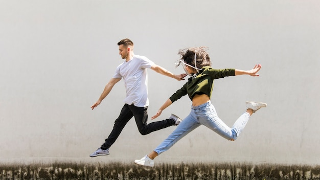 Active young couple jumping against grunge wall
