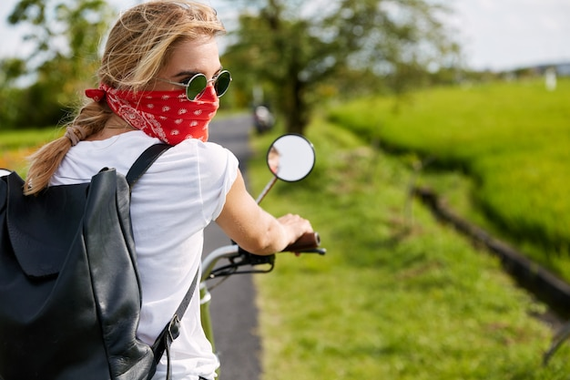 Active young female biker carries bag on back, wears sunglasses and covers face with bandana, rides on her favorite motorbike, rides on asphalt road, enjoys speed, spends leisure time outdoor