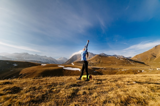 Active young girl in a blue jacket doing yoga in the background of the caucasian mountains