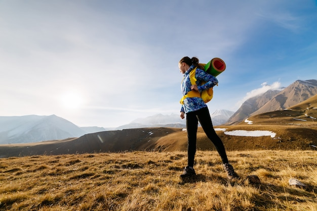 Active young girl in a blue jacket travels through the caucasus mountains with a backpack and tent