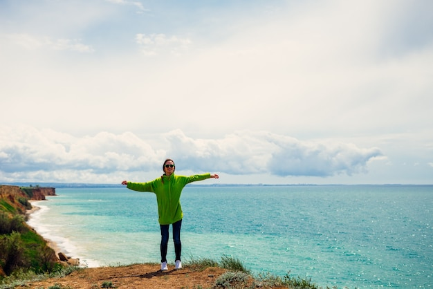 Active young girl in a green sweatshirt travels, against the sea