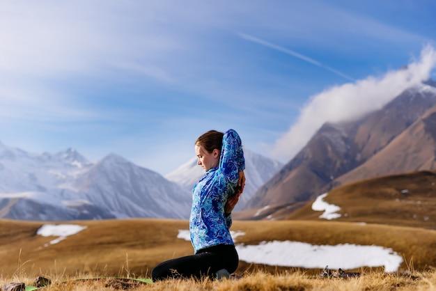 Активная молодая девушка в синей куртке занимается йогой на фоне кавказских гор
