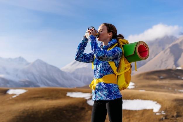 青いジャケットを着たアクティブな若い女の子は、熱いお茶を飲み、白人の尾根に沿って移動します