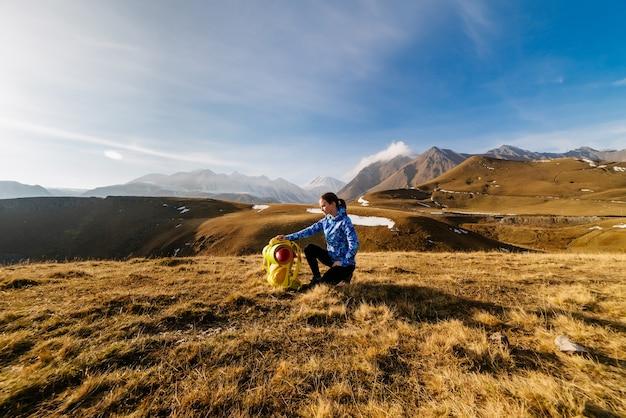 Активная молодая девушка в синей куртке сидит на фоне кавказских гор