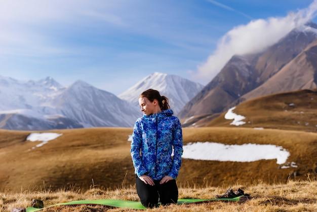 Активная молодая девушка в синей куртке сидит на фоне кавказского хребта и наслаждается природой