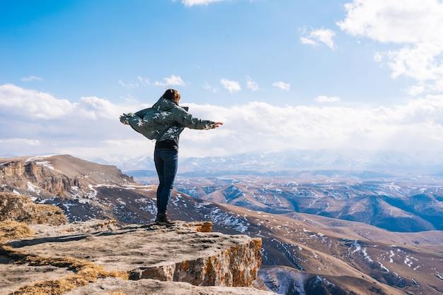 暖かいジャケットを着たアクティブな若い女の子は、山を旅し、自然ときれいな空気を楽しんでいます