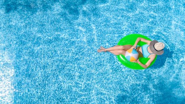 Активная молодая девушка в бассейне с высоты птичьего полета сверху, ребенок расслабляется и плавает на надувном кольце пончик и веселится в воде на семейный отдых, тропический курорт