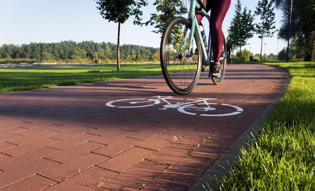 Active young girl rides on a bike path in a city park in the early morning. leisure concept.
