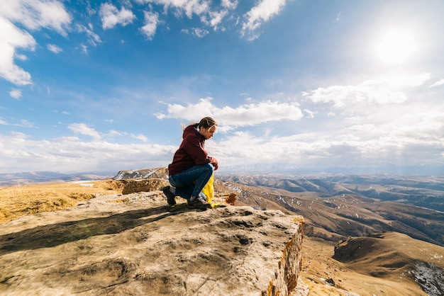 Active young girl sits at the edge of the mountain, enjoys nature and the sun, holds a yellow backpack