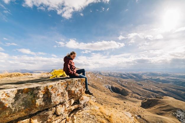 アクティブな若い女の子は、黄色のバックパックで崖の端に座って、山の自然と太陽を楽しんでいます