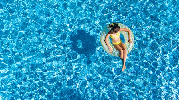 Active young girl in swimming pool aerial top view from above,
