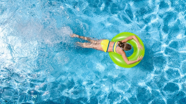 Active young girl in swimming pool aerial view child relaxes and swims on inflatable ring